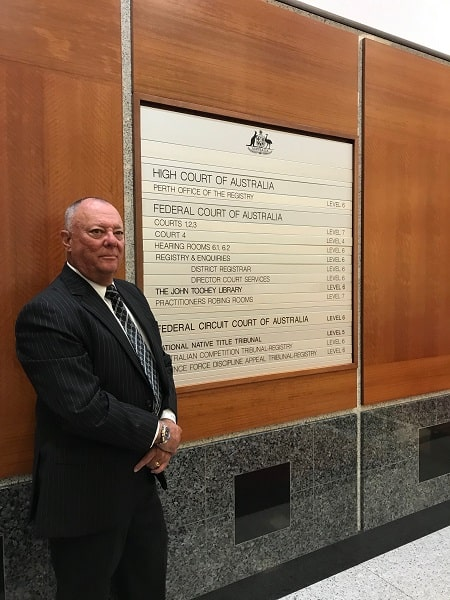 A Man wearing a black formal suit with a tie is standing behind a brown wooden wall with a picture frame about High Court Of Australia which is used in ASIC investigations by Criminal Lawyer Perth.