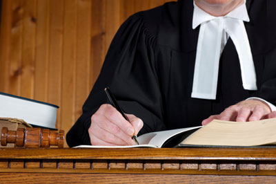 A judge sitting on a trial court, writing on a white notebook placed on a table and along with the brown gavel and books, which specify as on choosing a criminal lawyer in Perth.