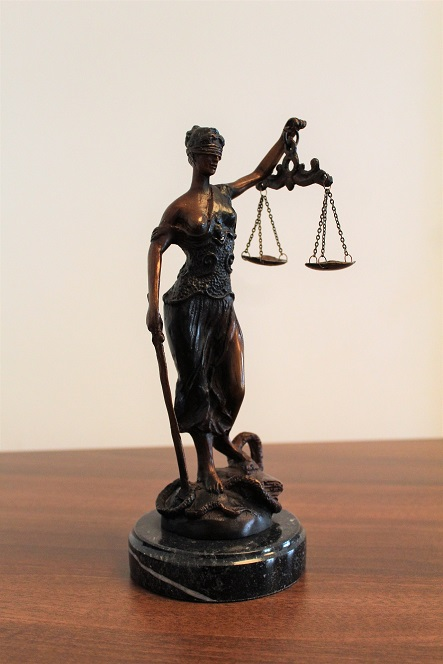 A lady justice mini statue placed on a wooden table and that symbolises the Criminal Law Special Application by Criminal Lawyers Perth.