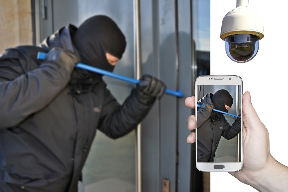 Closed-up of a hand holding a mobile phone and is taking a photo of a burglar trying to open the door. This is one of offences discussed by Criminal Lawyers Perth entitled Stealing & Home Burglary Offences.