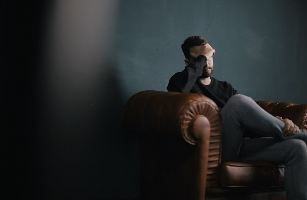 Man covering his head and eyes with his hand and is sitting on a brown couch and represents the professional association and misconduct inquiries discussed by the Criminal Lawyers Perth.
