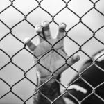 "Close-up of a man's hand holding to a fence, which is the header image of the blog ""capital punishment""."