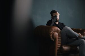 "Man covering his head and eyes with his hand and is sitting on a brown couch, which is the header image of the page entitled ""breaching offences""."