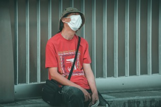 """Man with mask sitting on a side-walk that represent the blog """"criminal offence advice during covid-19""""."""